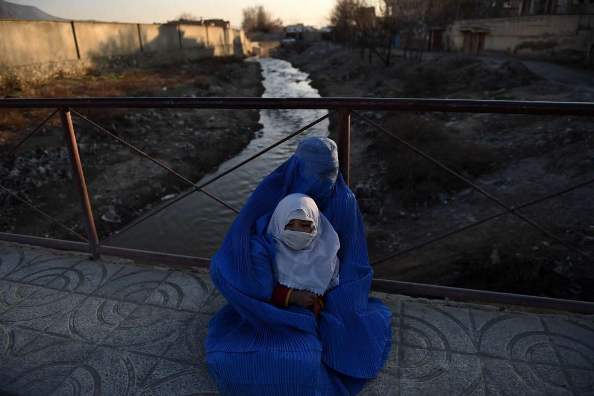 An Afghan woman holds a child as she begs on a bridge in Kabul on Feb 16, 2016. PHOTO: AFP/WAKIL KOHSAR