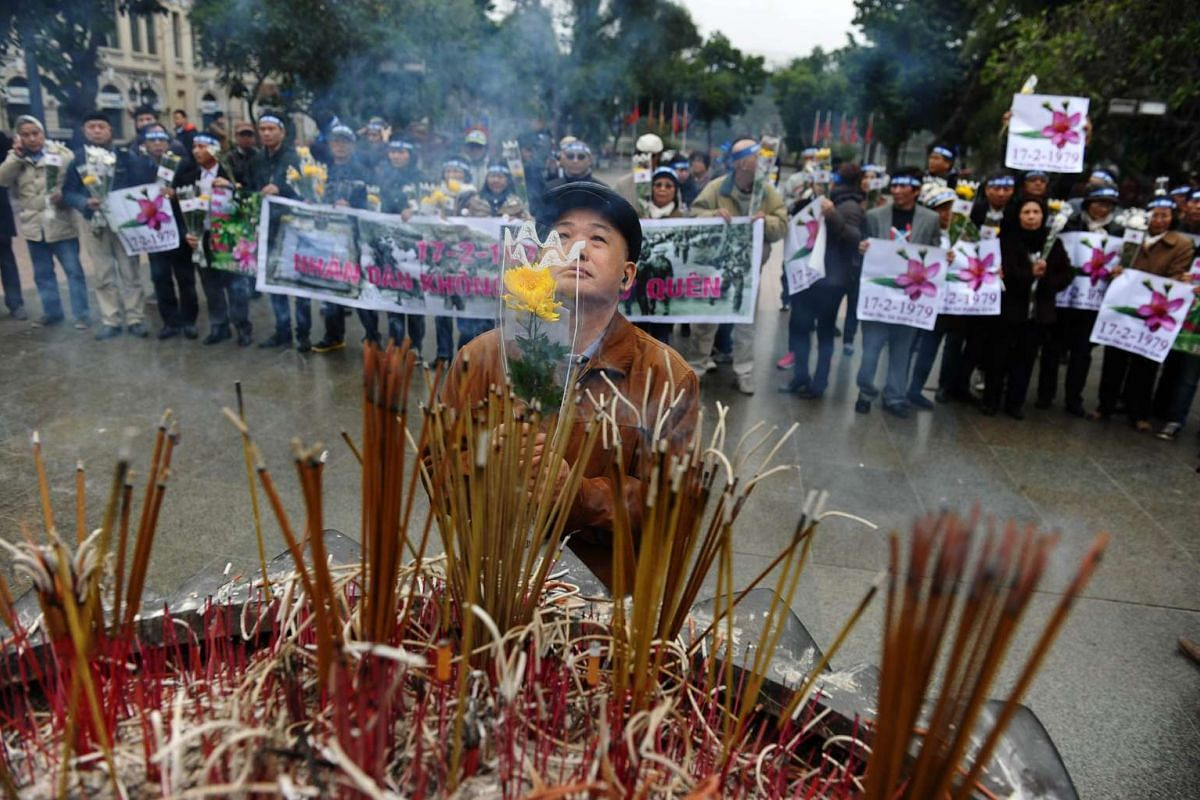 """An anti-China activist (C) prays as others hold posters reading """"February 17, 1979 - Our people will never forget"""" during an unofficial gathering in Hanoi on Feb 17, 2016, to mark the 37th anniversary of a bloody border war launched by China on Feb 1"""
