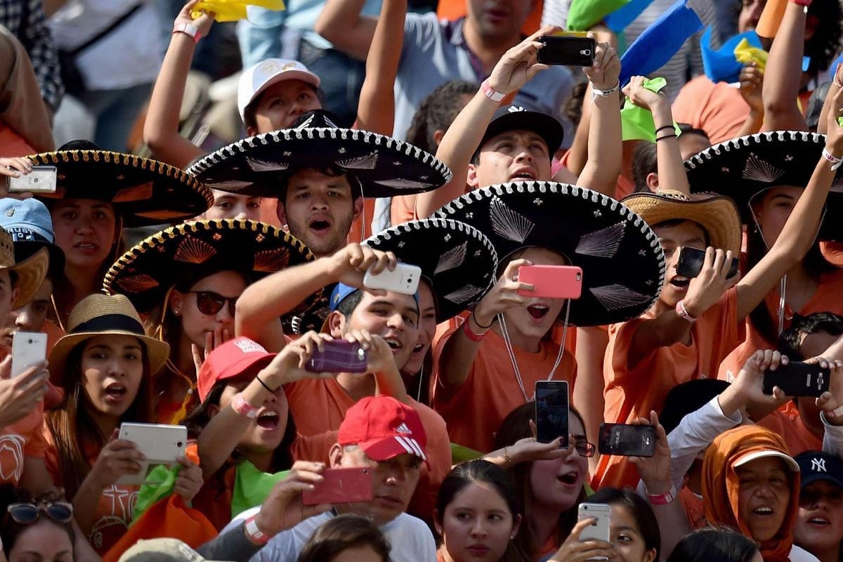 """People cheer as Pope Francis arrives for a meeting with young people at the """"Jose Maria Morelos y Pavon"""" stadium in Morelia on Feb 16, 2016. PHOTO:  AFP/GABRIEL BOUYS"""