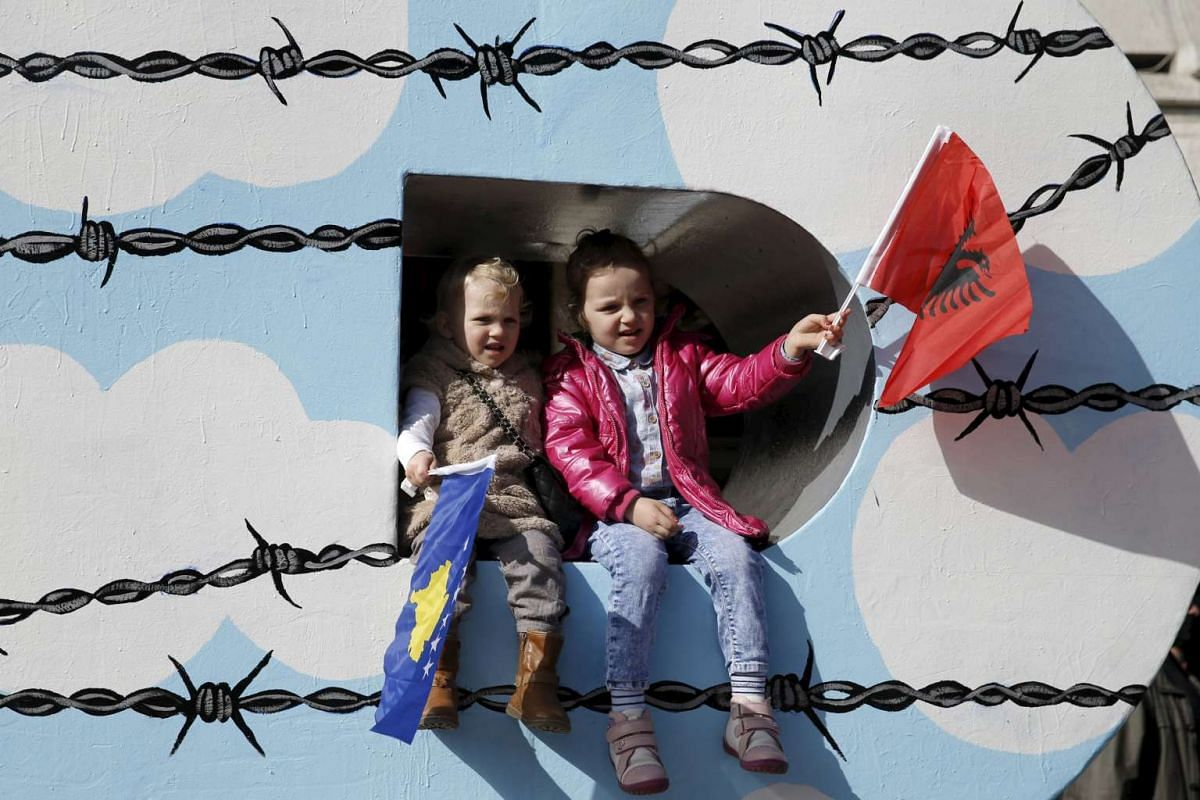 """Children wave Albanian (right) and Kosovar flags on the """"Newborn"""" monument during a celebration marking the eighth anniversary of Kosovo's declaration of independence from Serbia, in Pristina, on Feb 17, 2016. PHOTO: REUTERS/MARKO DJURICA"""