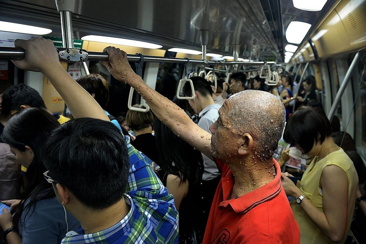 Mr Wee taking a crowded train home after a day of shopping in Chinatown. He is the youngest of six siblings and the only one affected by neurofibromatosis. He said he is close to his family and sees his siblings about once a month. Mr Wee in Chinatow