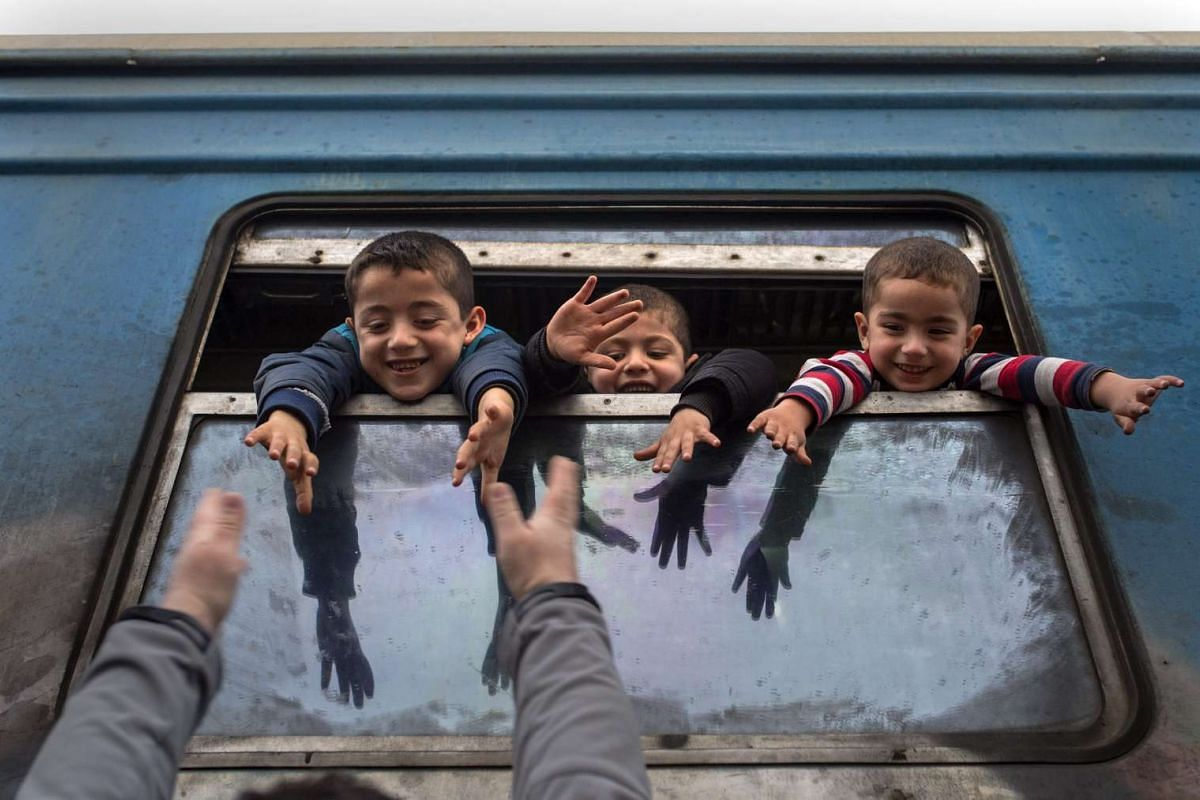 Refugee children wave from the windows of the train heading for Serbia, near Gevegelia, The Former Yugoslav Republic of Macedonia, Feb 18, 2016. PHOTO: EPA/GEORGI LICOVSKI