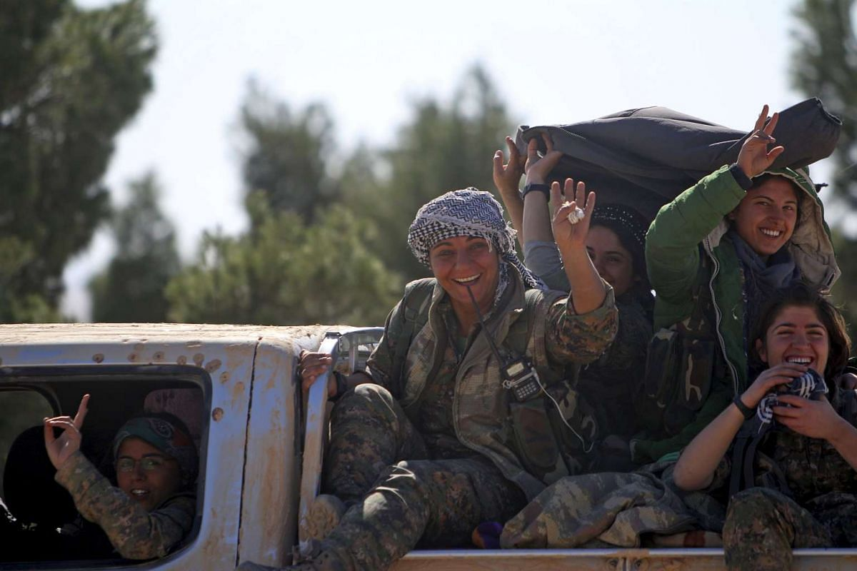 Democratic Forces of Syria women fighters gesture while riding a pick-up truck near al-Shadadi town, Hasaka countryside, Syria, Feb 18, 2016. PHOTO: REUTERS/RODI SAID