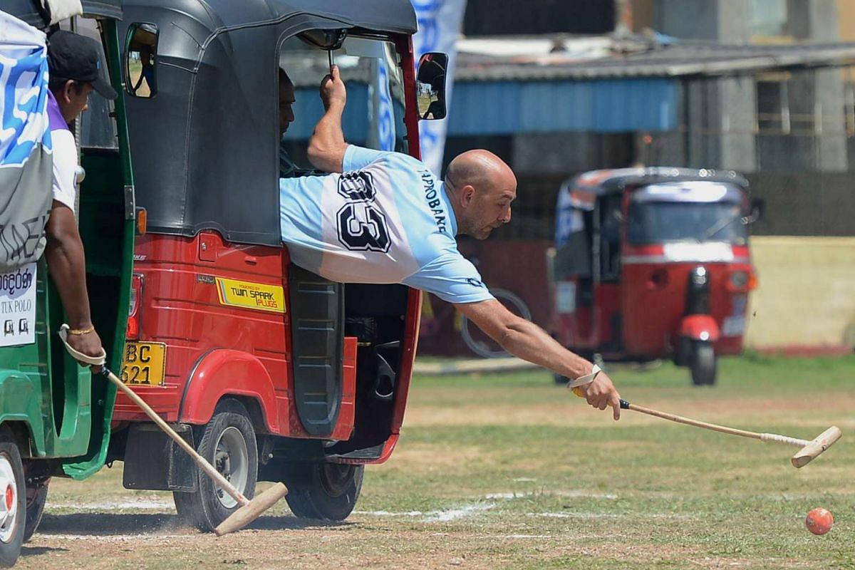 Players take part in in a tuk-tuk (three-wheeler) polo match as part of a promotional event organized by a local Sri Lankan leasing company in the southern town of Galle on February 21, 2016. PHOTO: AFP/LAKRUWAN WANNIARACHCHI