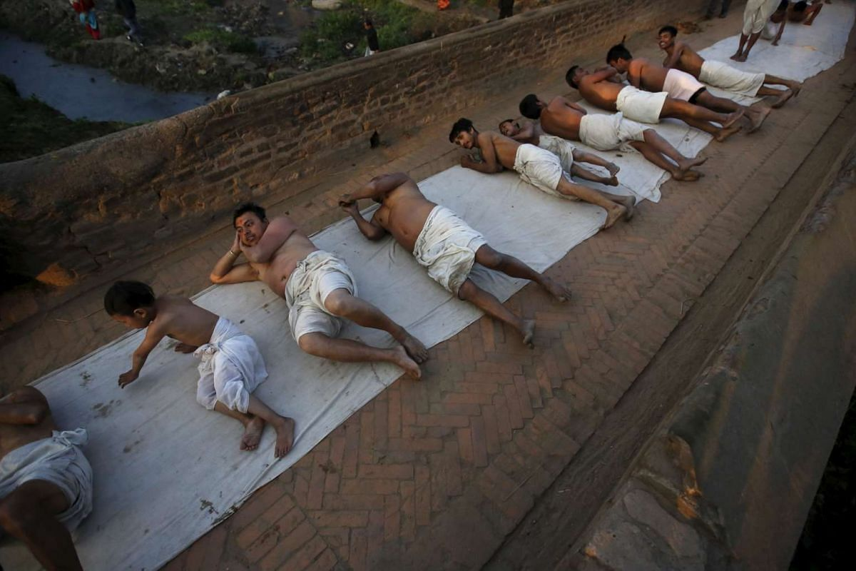 Devotees offer prayers by rolling on the ground after a bathing ritual on Feb 22, 2016.