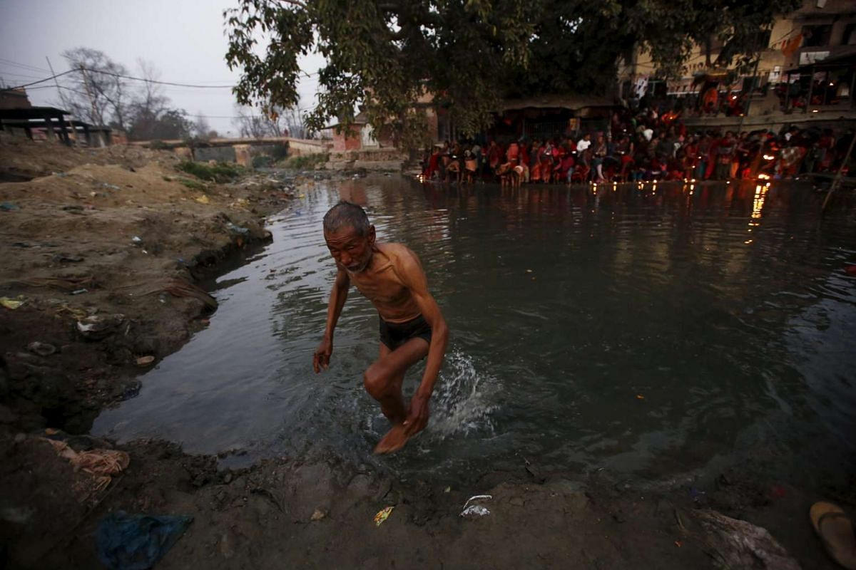 A devotee walks out from the Hanumante River after a bathing ritual on Feb 22, 2016.