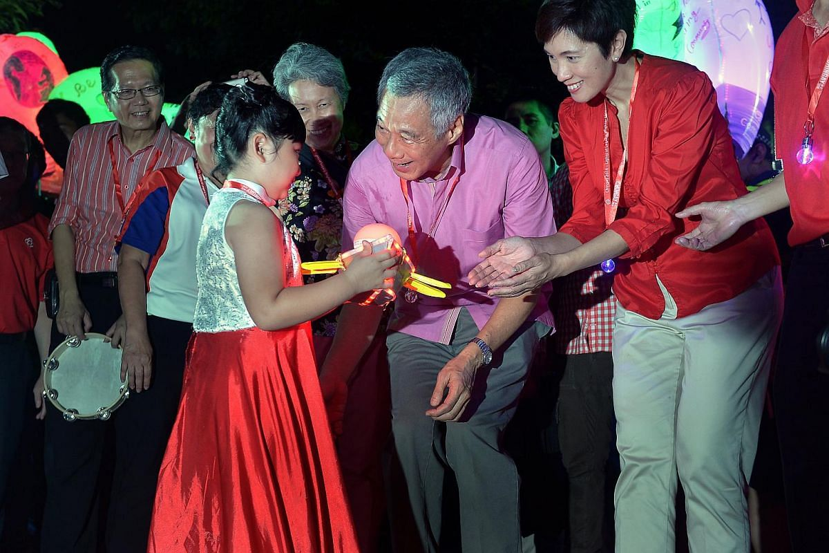 PM Lee Hsien Loong presenting a small lighted boat named Voyage SG 100 to seven-year-old, Nathania Koh.