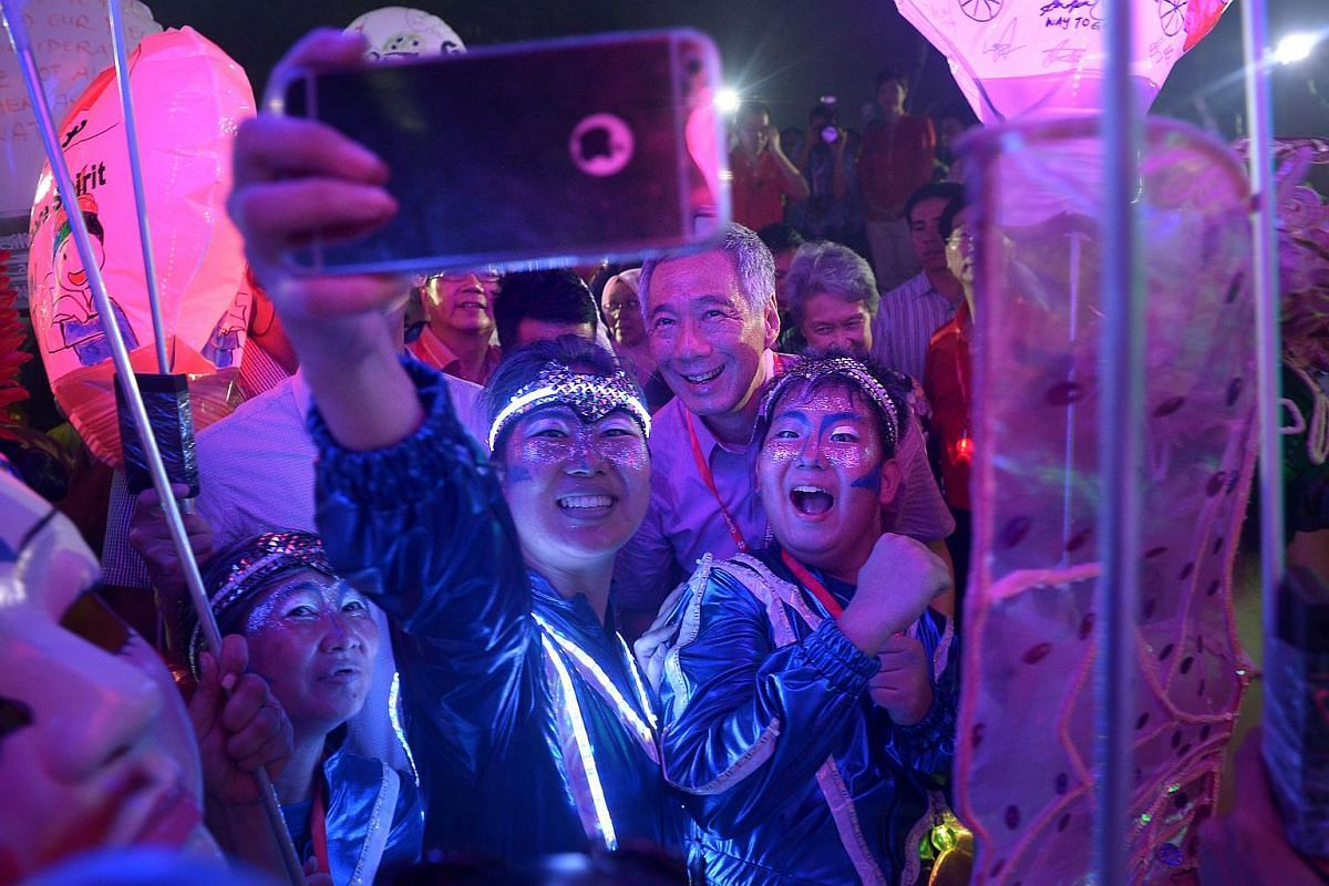 PM Lee Hsien Loong takes a wefie with siblings, Zhao Yi Ling, 22 a student at NUS (with phone) and Zhao Yi Cong, 13, a student (right).