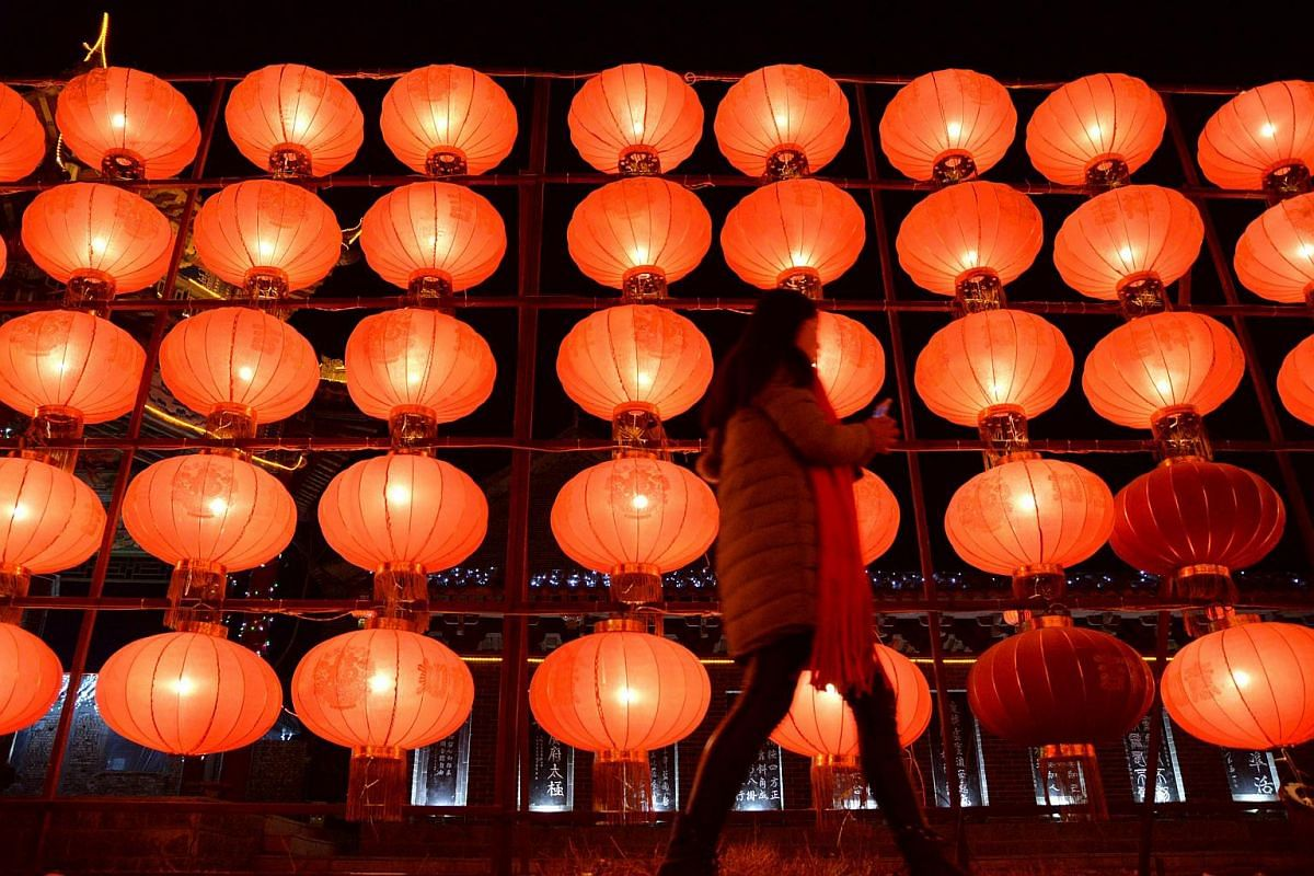 A woman walking past lanterns at an exhibition of lanterns in a square in Handan, in China's northern Hebei province, on Feb 20, 2016.