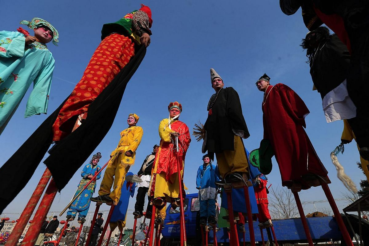 Chinese folk entertainers walking on stilts during a folk art performance event in rural Zhangjiakou city, China's Hebei province, on Feb 21, 2016.