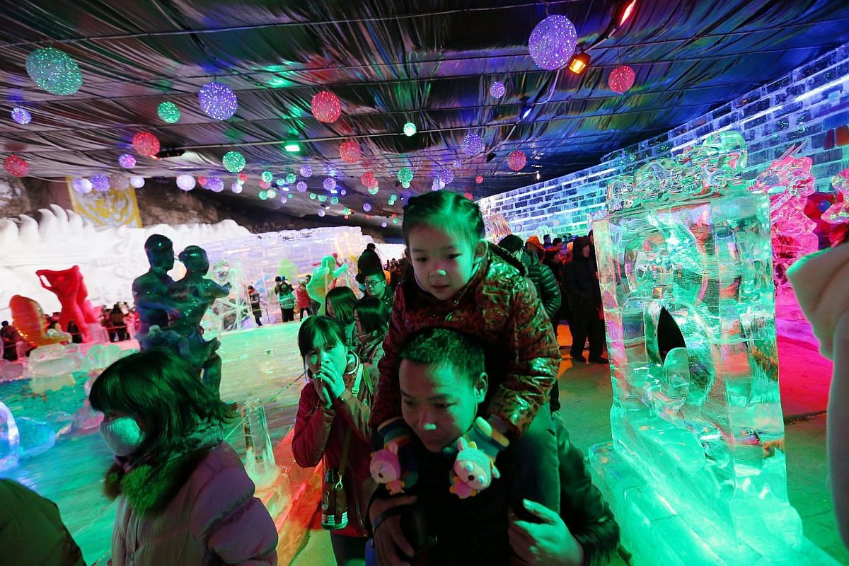 Visitors looking at colourfully lighted ice sculptures at Longqingxia Ice Lantern Festival in Yanqing district of Beijing, on Feb 20, 2016.