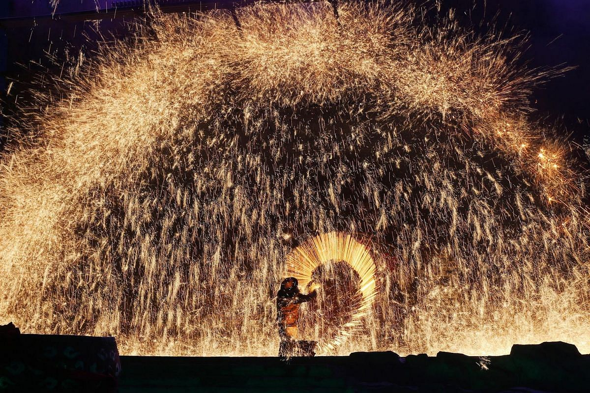 A performer spraying molten iron against a cold stone city wall to create sparks like fireworks in the rural Zhangjiakou city, China's Hebei province, on Feb 21, 2016.