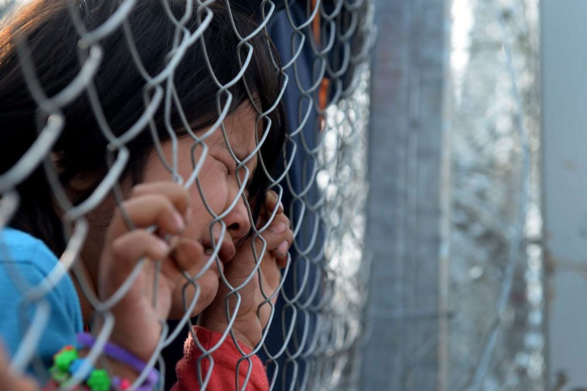 A migrant girl holds onto wire fencing at the Greek-Macedonian border, near the Macedonian city of Gevgelija, Feb 22, 2016. Macedonia confirmed that it is only allowing Syrian and Iraqi refugees through. PHOTO: EPA
