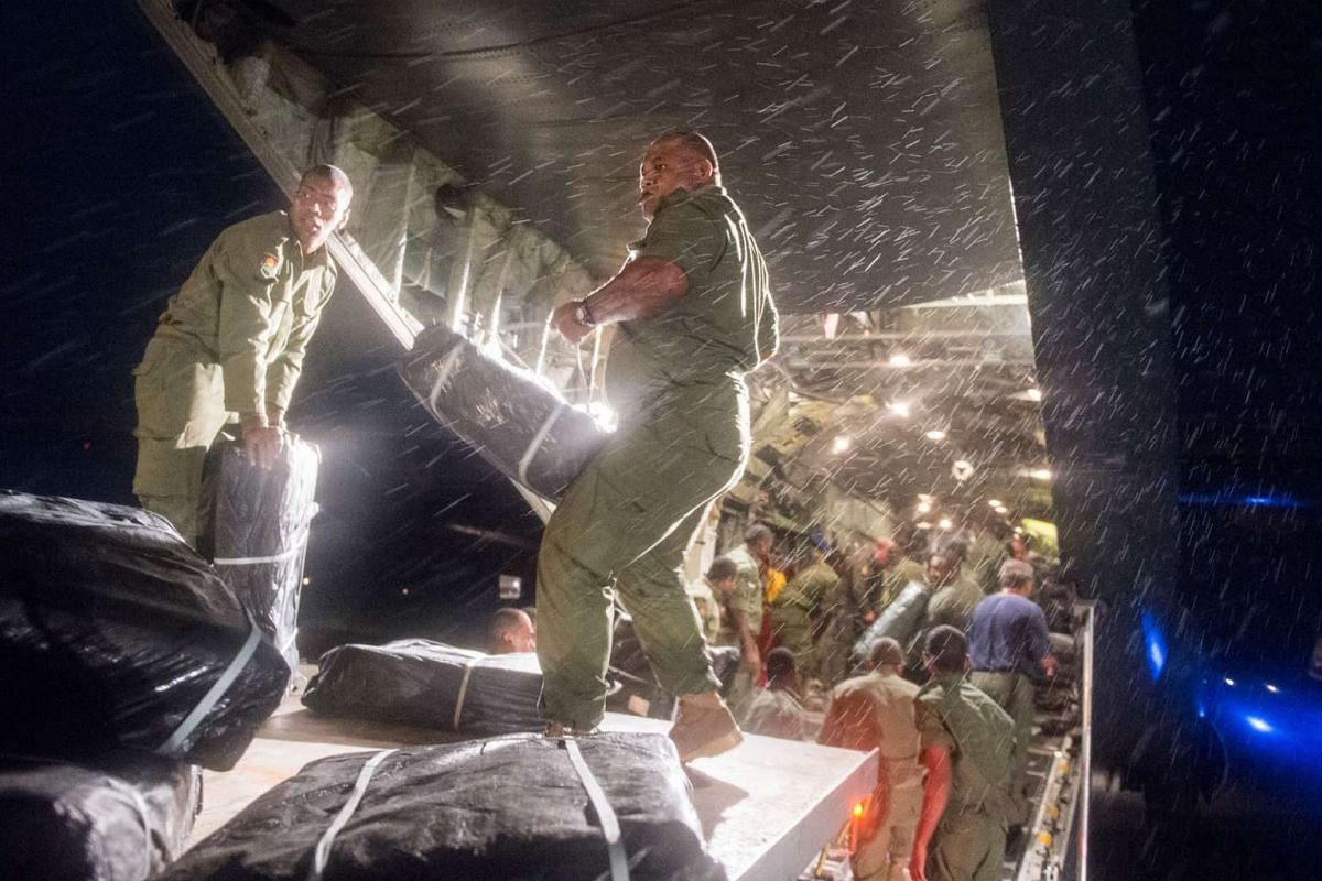 In this handout photo dated Feb 23, 2016, received from the New Zealand Defence Force shows aid supplies being unloaded by Fijian soldiers from a RNZAF C-130 Hercules transport plane in Fiji's capital Suva, following Tropical Cyclone Winston that hit