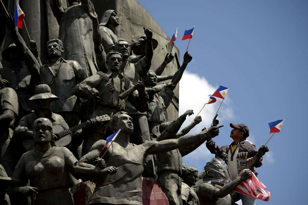 Renato Vallarte (R), a worker from the Spirit of EDSA Foundation, attaches flags to the statues at the People Power Monument two days before the anniversary of the People Power revolution in Manila on Feb 23, 2016. PHOTO: AFP