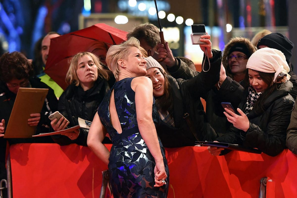 Actress Trine Dyrholm (front) poses for fans as she arrives to the premiere of Kollektivet (The Commune) at the 66th annual Berlin International Film Festival.