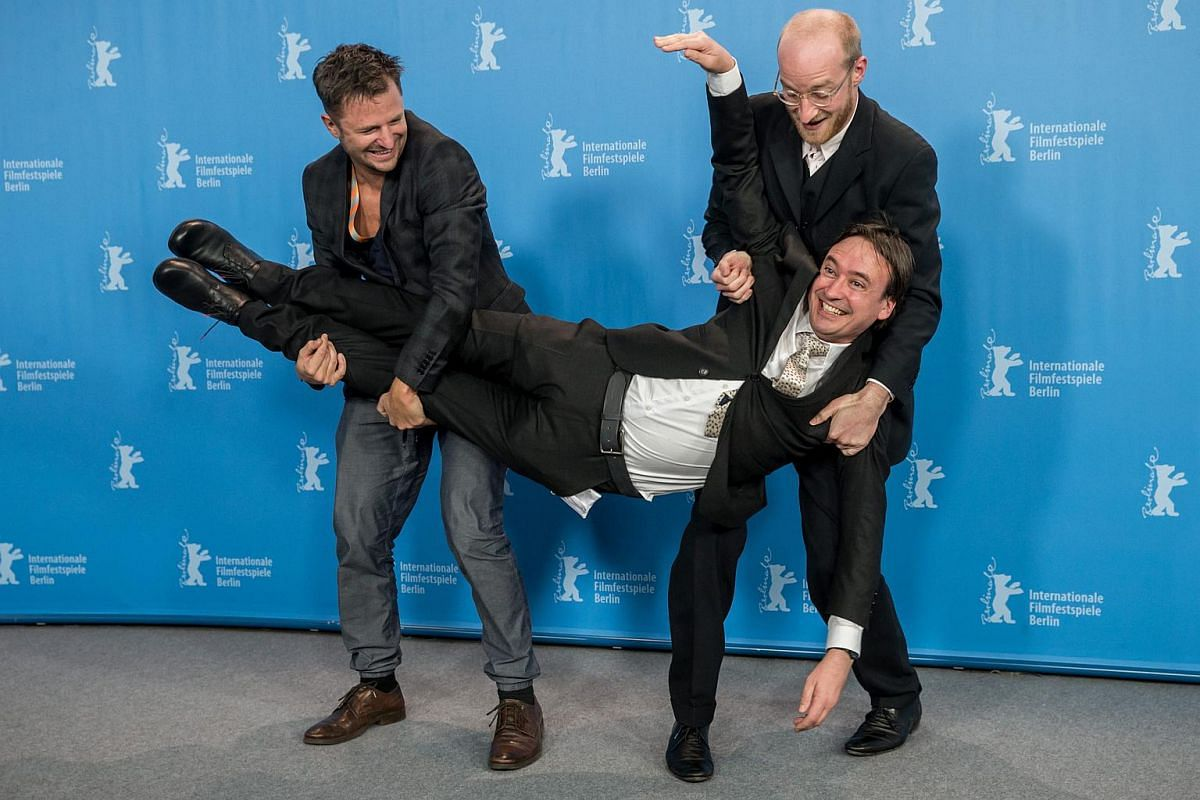 Philipp Hochmair (left) and Lukas Turtur pose holding director Klaus Haendl (front) during a photocall for Tomcat at the 66th annual Berlin International Film Festival.