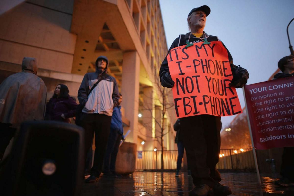 """About a dozen protestors demonstrated outside the FBI's J. Edgar Hoover headquarters in support of Apple and against a move by the federal government to force the computer company to create a """"backdoor"""" to the iPhone Feb 23, 2016, in Washington, DC."""