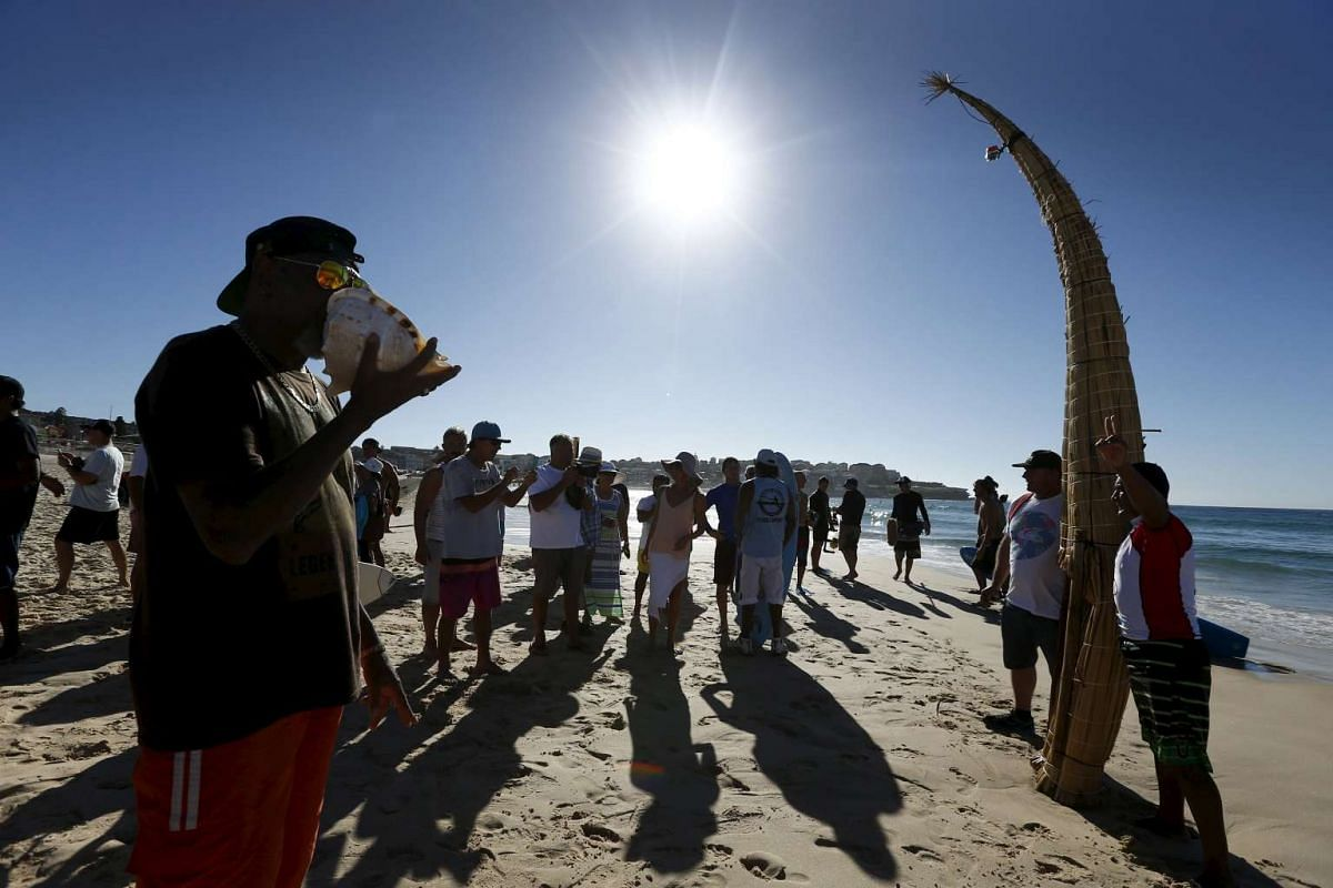 """Peruvian surfer Carlos 'Huevito' Areola (right) poses alongside his reed board, or """"caballito"""" (little horse), as a man plays a shell (left) in celebration of Huevito's first surf at Sydney's Bondi Beach."""
