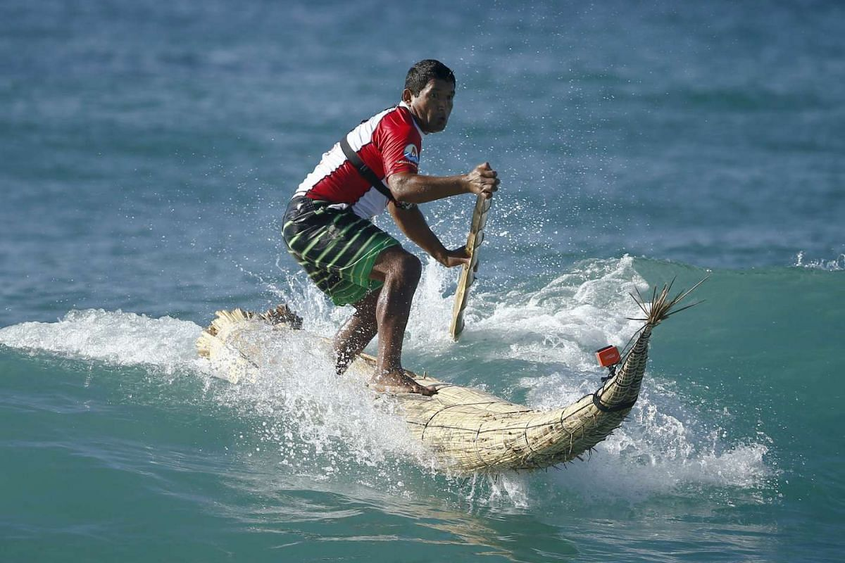 "Peruvian surfer Carlos 'Huevito' Areola rides a reed board, or ""caballito"" (little horse), at Sydney's Bondi Beach."