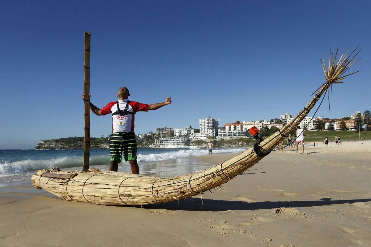 """Peruvian surfer Carlos 'Huevito' Areola celebrates alongside his reed board, or """"caballito"""" (little horse), after his first surf run at Sydney's Bondi Beach."""