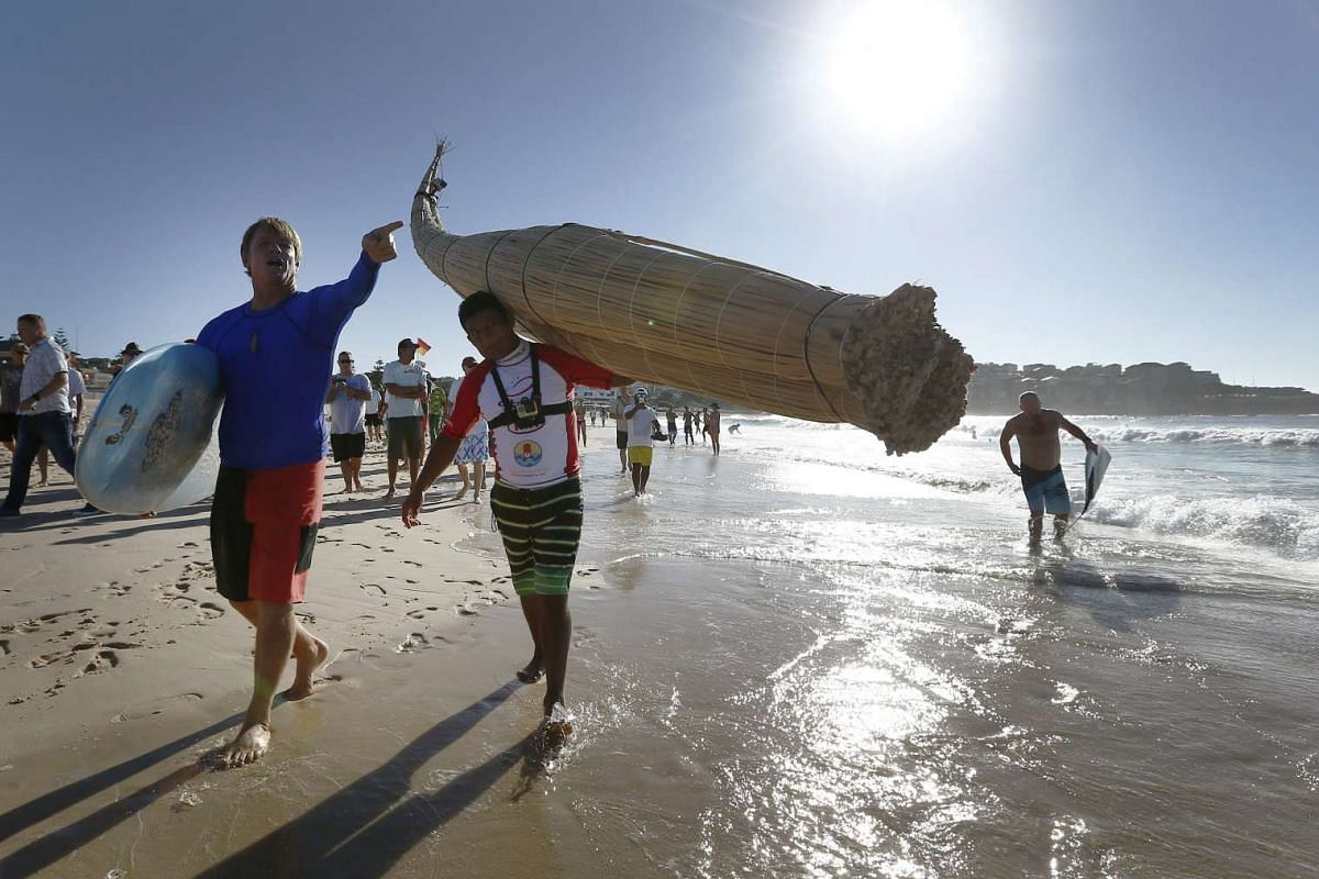 "Australian champion surfer Cheyne Horan guides Peruvian surfer Carlos 'Huevito' Areola, carrying his reed board, or ""caballito"" (little horse), into the ocean at Sydney's Bondi Beach."