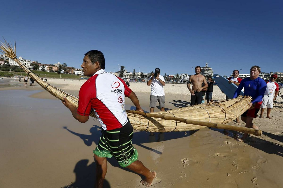 "Australian champion surfer Cheyne Horan (right) guides Peruvian surfer Carlos 'Huevito' Areola, carrying his reed board, or ""caballito"" (little horse), into the ocean at Sydney's Bondi Beach."