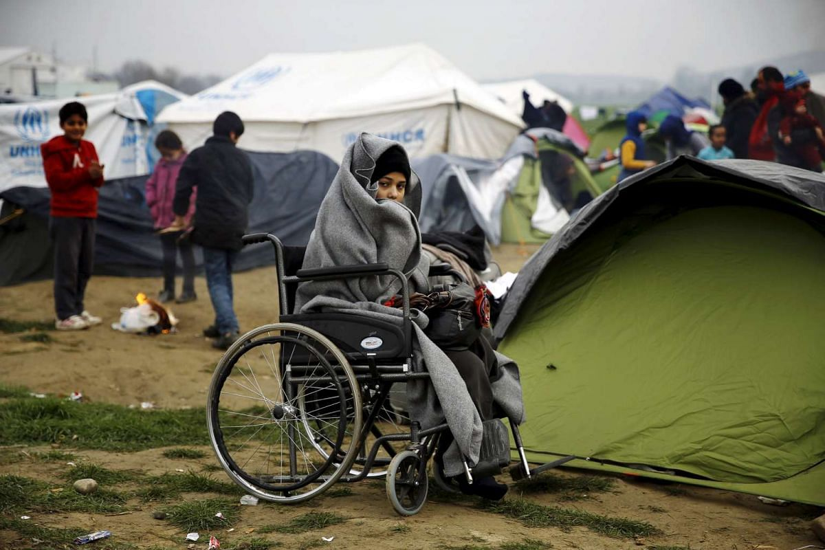 A temporarily stranded Syrian refugee is seen in a wheelchair on a field at a makeshift camp next to the Greek-Macedonian border, near the Greek village of Idomeni, Feb 24, 2016. PHOTO: REUTERS/YANNIS BEHRAKIS