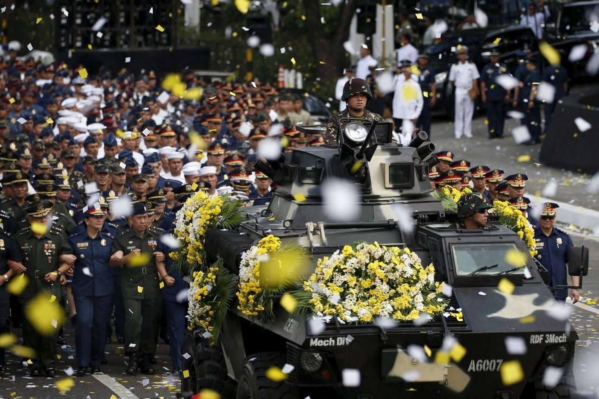 Soldiers and police officers link arms as they march behind a Philippine military armored vehicle decorated with flowers during a celebration of the 30th anniversary of the EDSA People Power Revolution, in Quezon City, Metro Manila, Feb 25, 2016. PHO