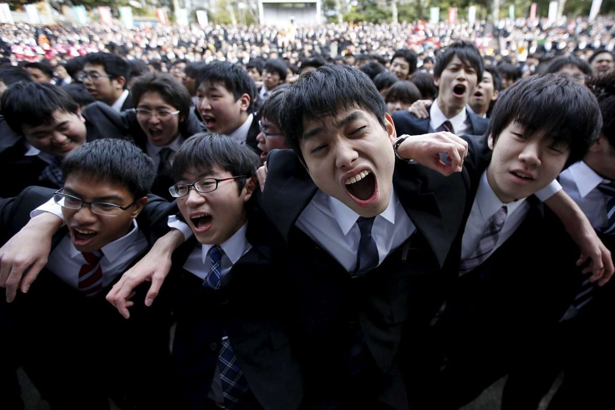 Japanese college students shout slogans during a pep rally held to boost their morale ahead of their job hunt, at an outdoor theatre in Tokyo, Feb 25, 2016. PHOTO: REUTERS/ISSEI KATO