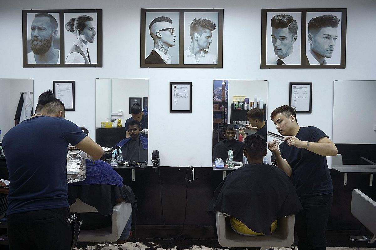 Above: The dorm's management provides enough benches for residents to rest during their down time, and enough power outlets in the rooms for them to charge phones and other devices. Below: Residents getting haircuts at a barber shop staffed by former