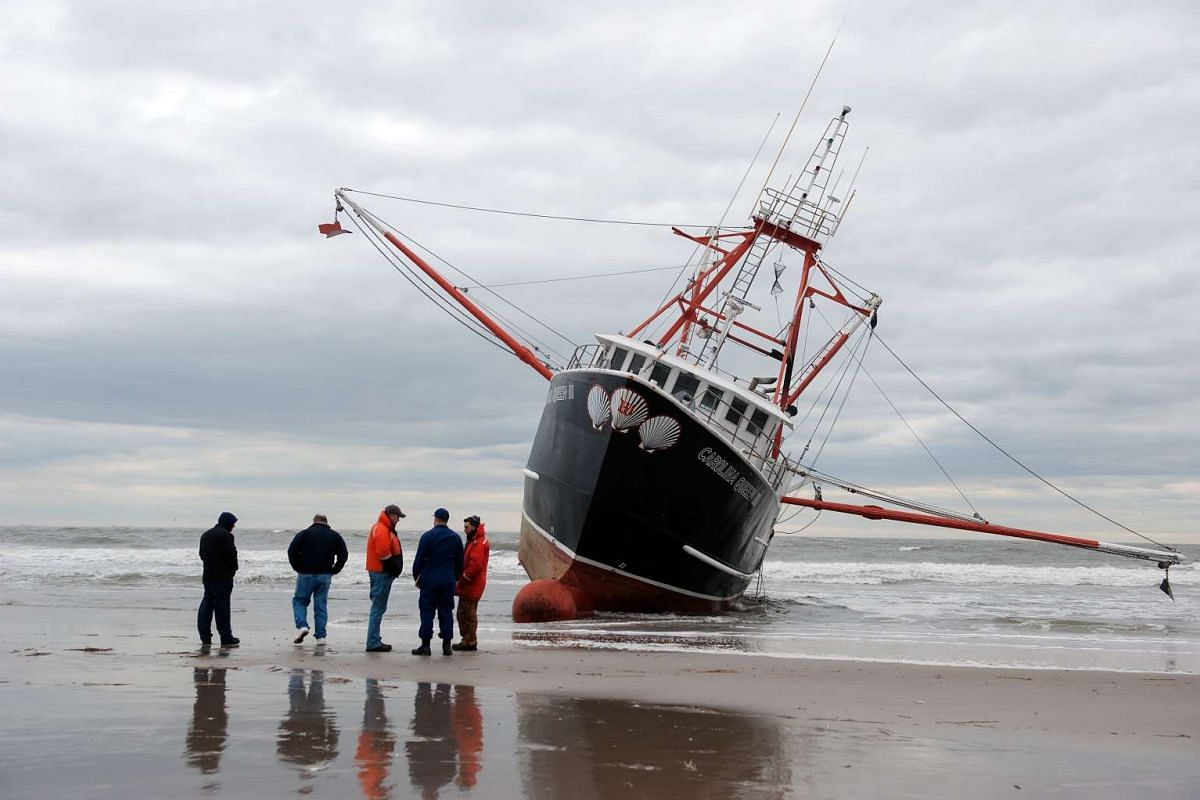 A group, including several United States Coast Guard members, stands in front of an aground fishing vessel on the shore of Rockaway Beach on February 25, 2016 in Queens, NY. The fishing vessel ran aground during stormy seas and strong winds the night