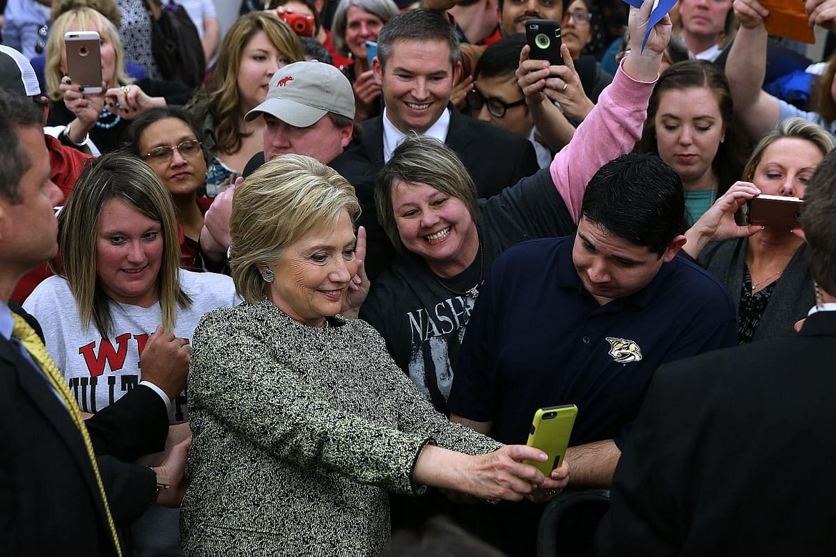 Mr Sanders (right) greeting supporters in Colorado as he campaigned on Sunday for the Democratic Party's nomination to be US president. His rival, Mrs Clinton (far right), was on the campaign trail in Tennessee on the same day.