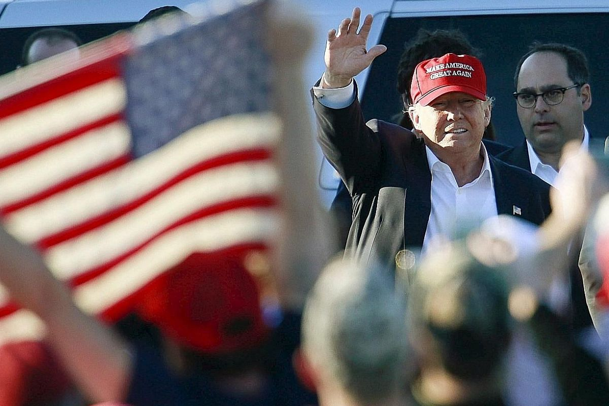 Mr Trump waving as he arrived at a rally at Madison City Schools Stadium in Madison, Alabama, on Sunday. His Republican rivals, Mr Rubio and Mr Cruz, criticised him for failing to condemn a former Ku Klux Klan leader who had supported him on a radio