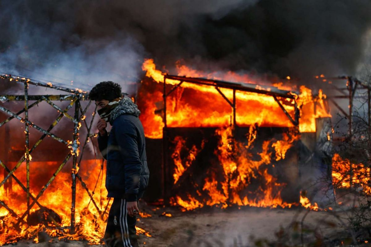 A refugee watching a shelter burn during the start of the expulsion of a part of the Jungle migrant camp in Calais, France, on Feb 29, 2016.
