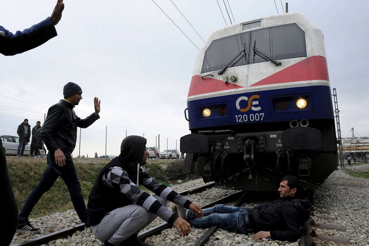 Stranded refugees sitting on railway tracks, blocking the way to a train, during a protest at the Greek-Macedonian border as they wait for the border crossing to reopen near the Greek village of Idomeni, on Feb 28, 2016.