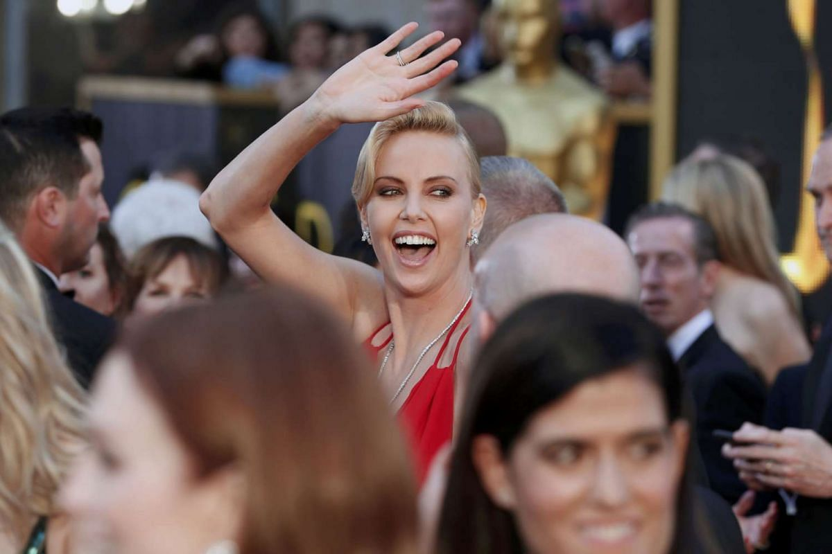 Presenter Charlize Theron, wearing a red Dior gown with a plunging neckline and US$3.7 million (S$5.2 million) in Harry Winston jewels, arriving at the 88th Academy Awards on Feb 28, 2016