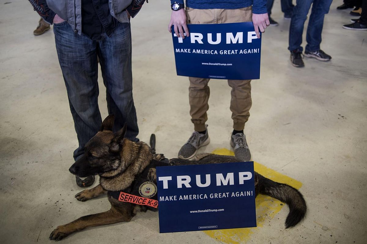 Attendees holding signs while standing by a service dog during a campaign rally for Republican presidential candidate Donald Trump at the Port Columbus International Airport in Ohio on March 1, 2016.