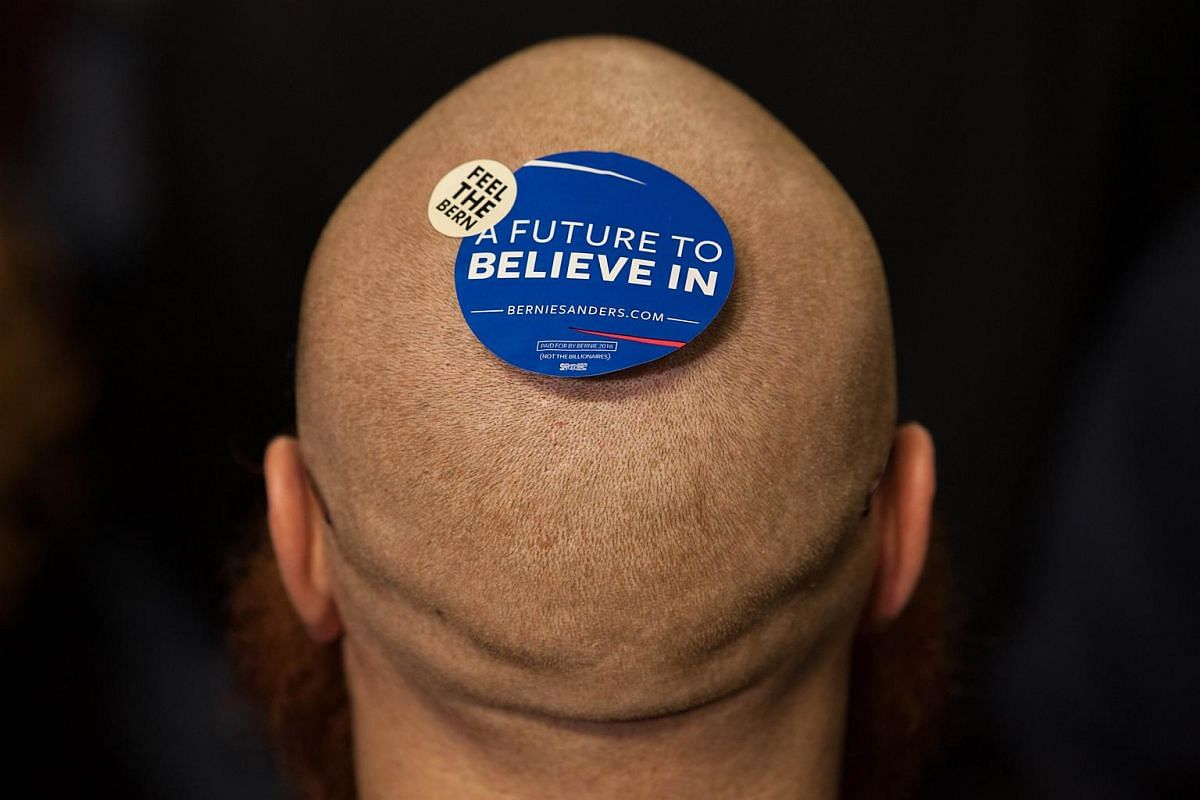 A supporter of Democratic presidential candidate Senator Bernie Sanders wearing a sticker on his head at a rally at the University of Massachusetts on Feb 22, 2016.