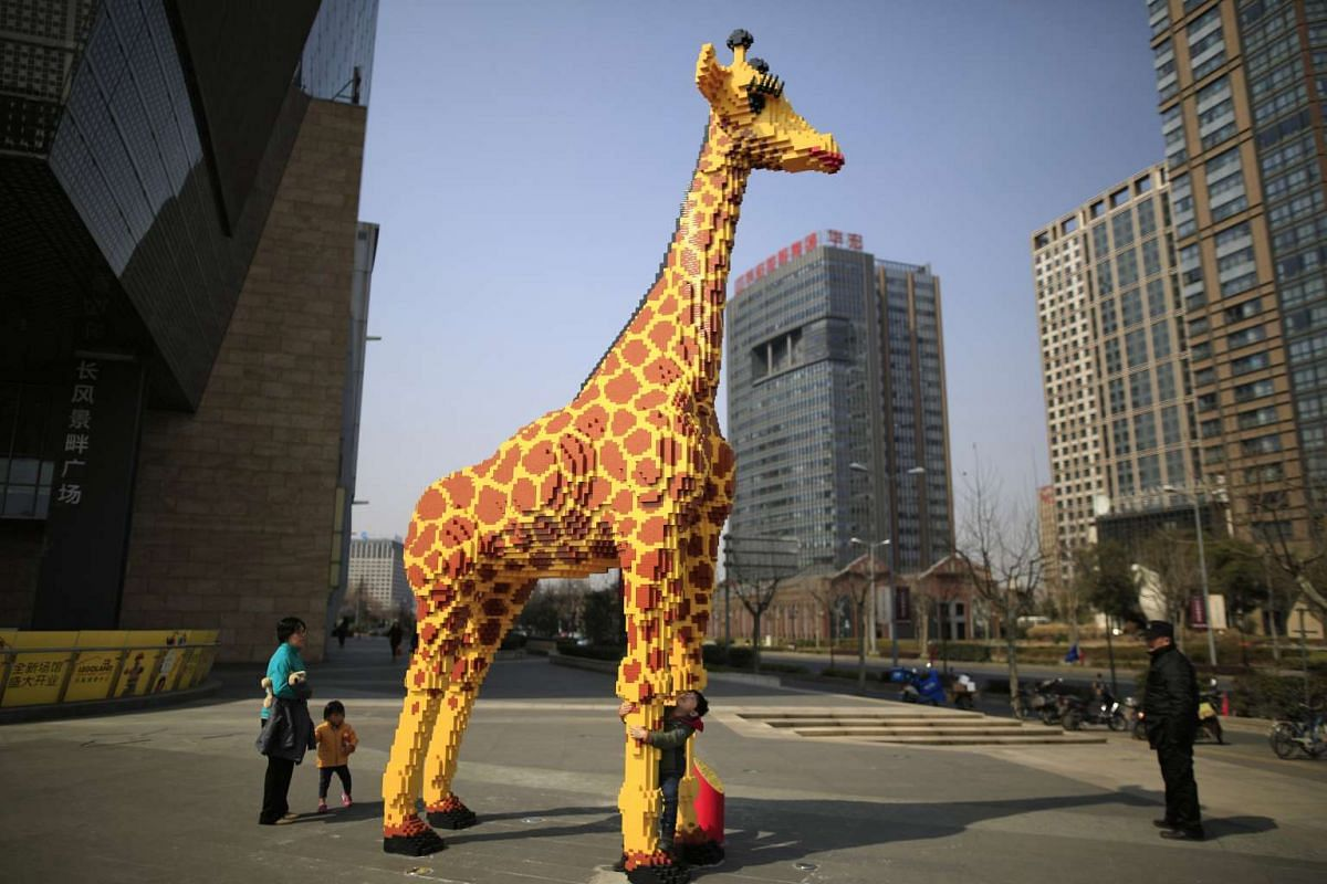 A 6.16-metre tall Lego giraffe is seen next to a shopping mall in Shanghai, China, on March 1, 2016. According to the local media, workers spent 450 hours building the giraffe.