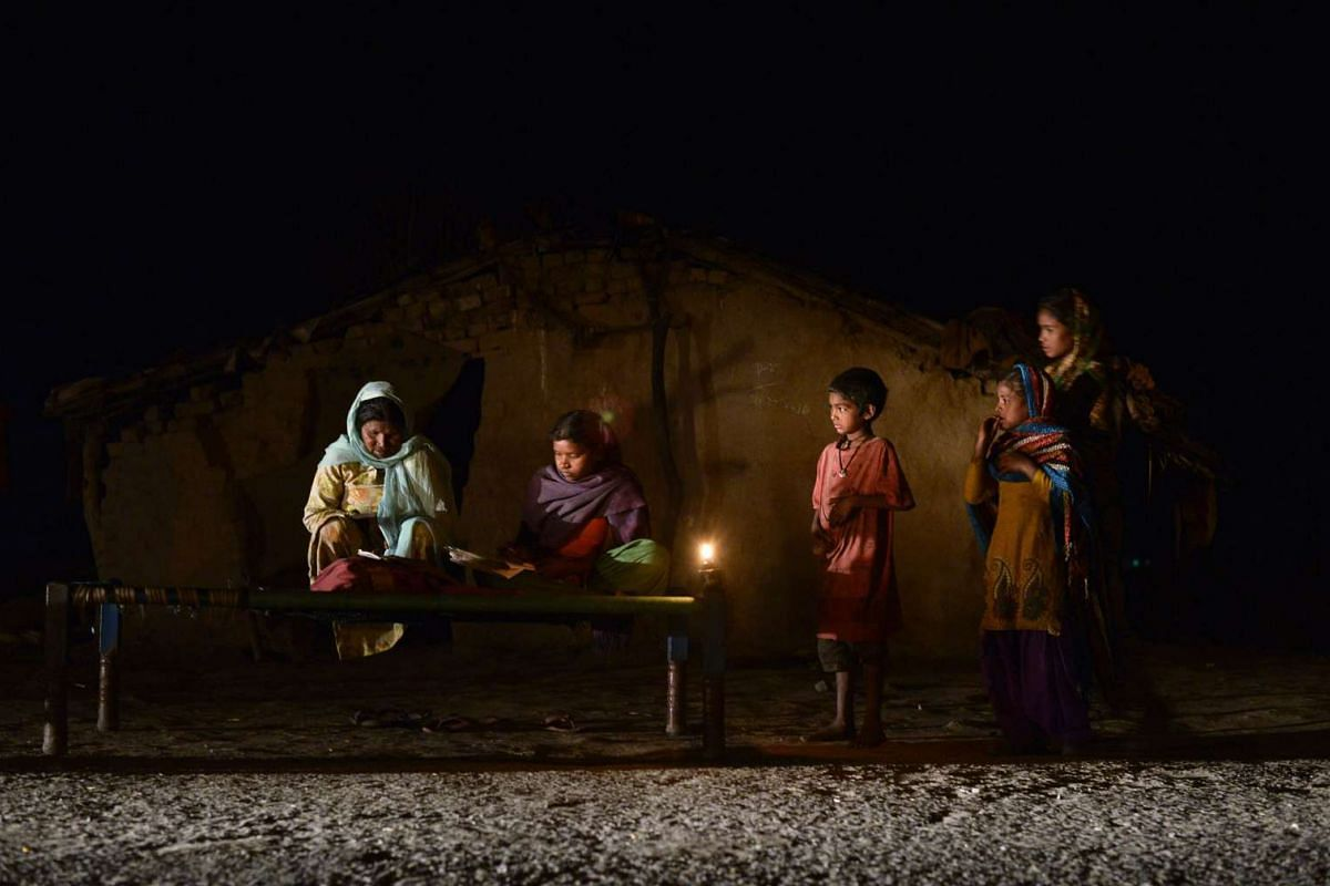 An Indian girl (centre) studying by candle light in a slum area without electric power in Phillaur, around 50km from Jalandhar, on Feb 29, 2016.