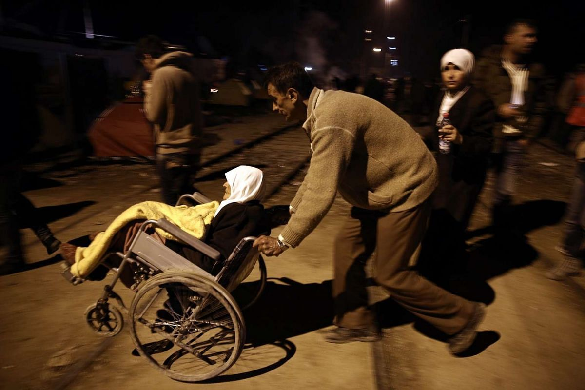 An elderly migrant woman is being assisted as refugees enter the camp in Idomeni, Greece, on March 1, 2016.