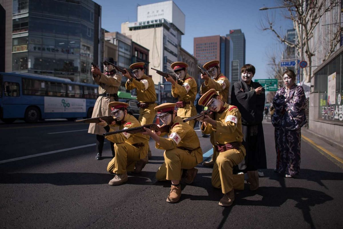 Activists dressed as colonial-era Japanese soldiers performing a mock execution during an anti-Japan protest marking the 97th Independence Movement Day in Seoul on March 1, 2016.