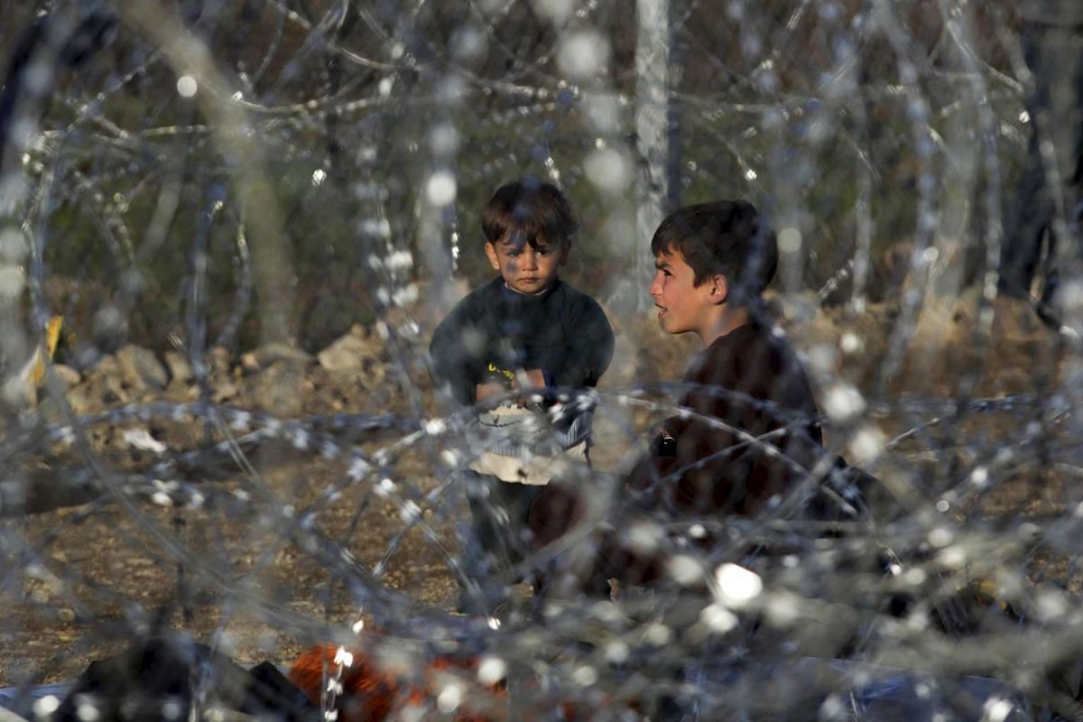 Boys are seen through barbed wire next to the Greek-Macedonian border, near the Greek village of Idomeni, on March 1, 2016.