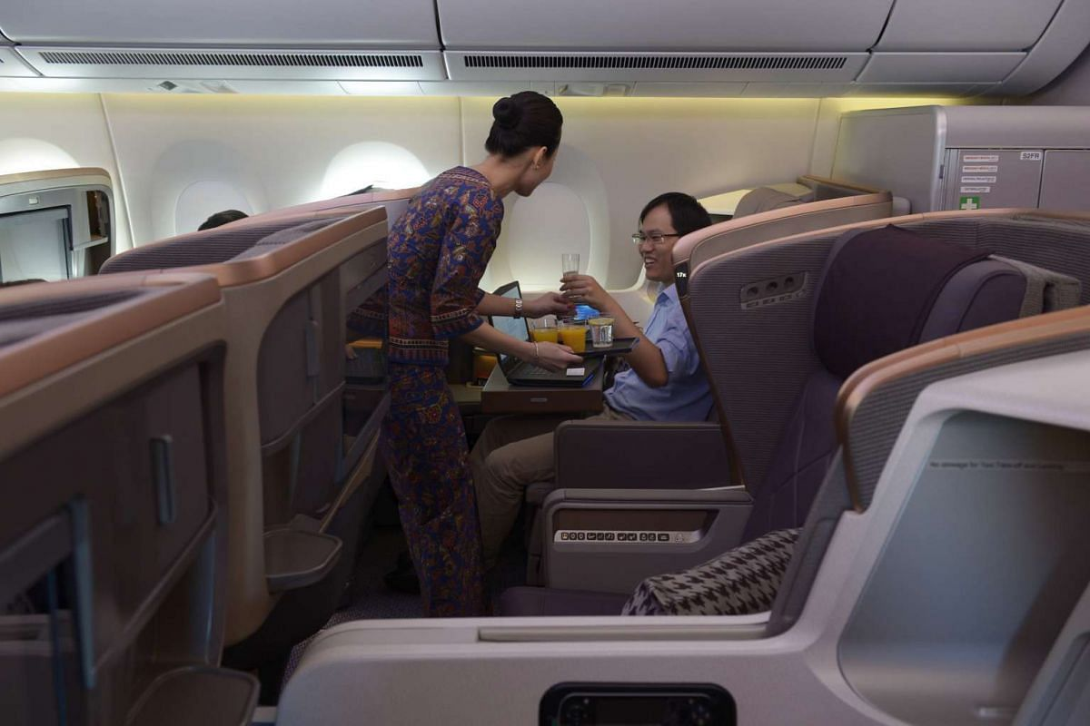 A Singapore Airlines stewardess serving drinks to a member of the media in the A350's business class cabin.