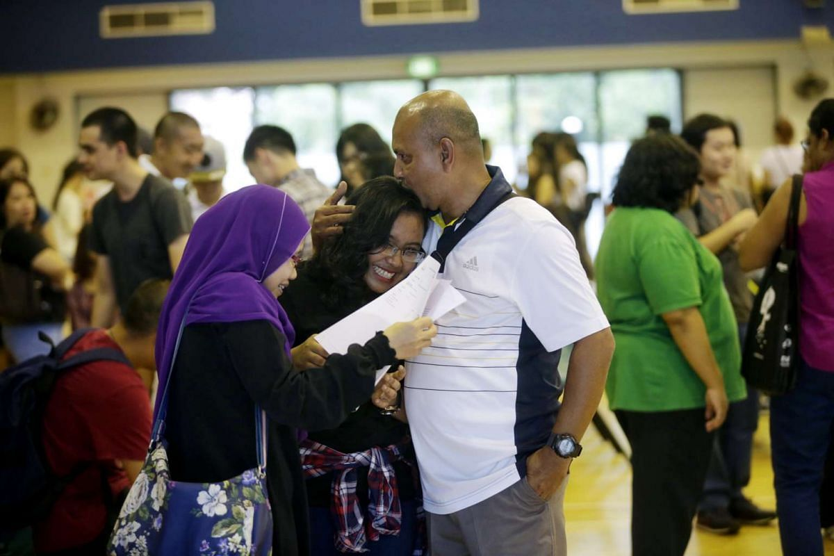 Feera Syaqirah Saaduddin receives a hug from her father while her mother looks at her A-level results at Millennia Institute on March 4, 2016.