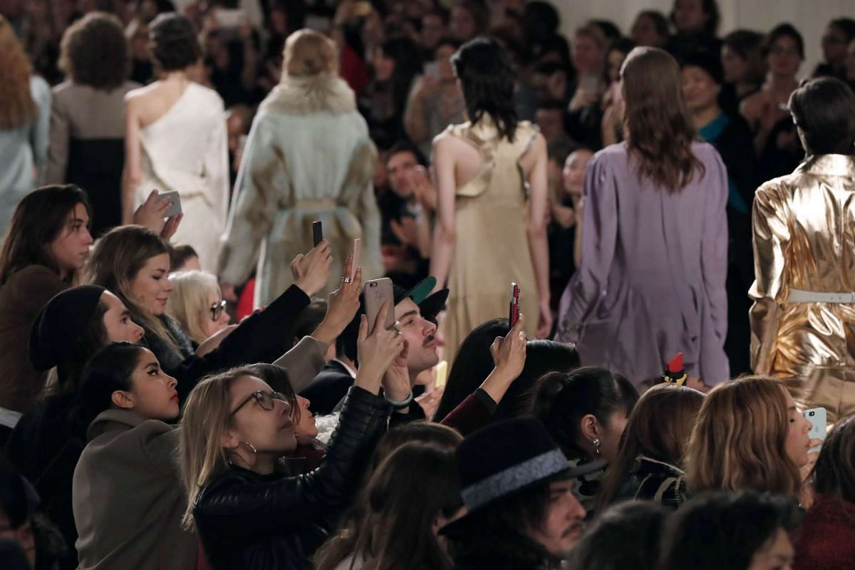 People take pictures at the end of the Lanvin fashion show during the 2016-2017 Fall/Winter collection, on March 3, 2016 in Paris.