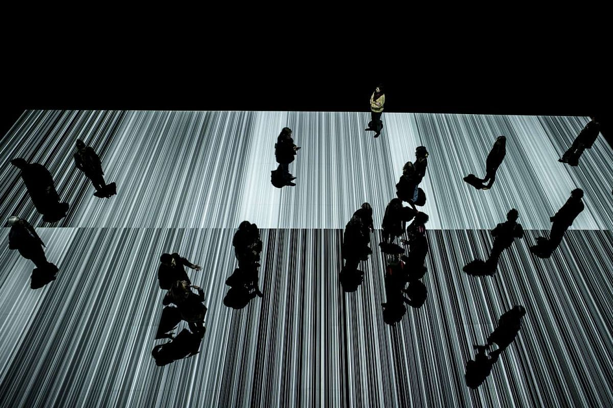 People walking in an artwork called Supercodex, designed by Japanese artist Ryoji Ikeda, in the Confluence museum in Lyon, France, on March 1, 2016.