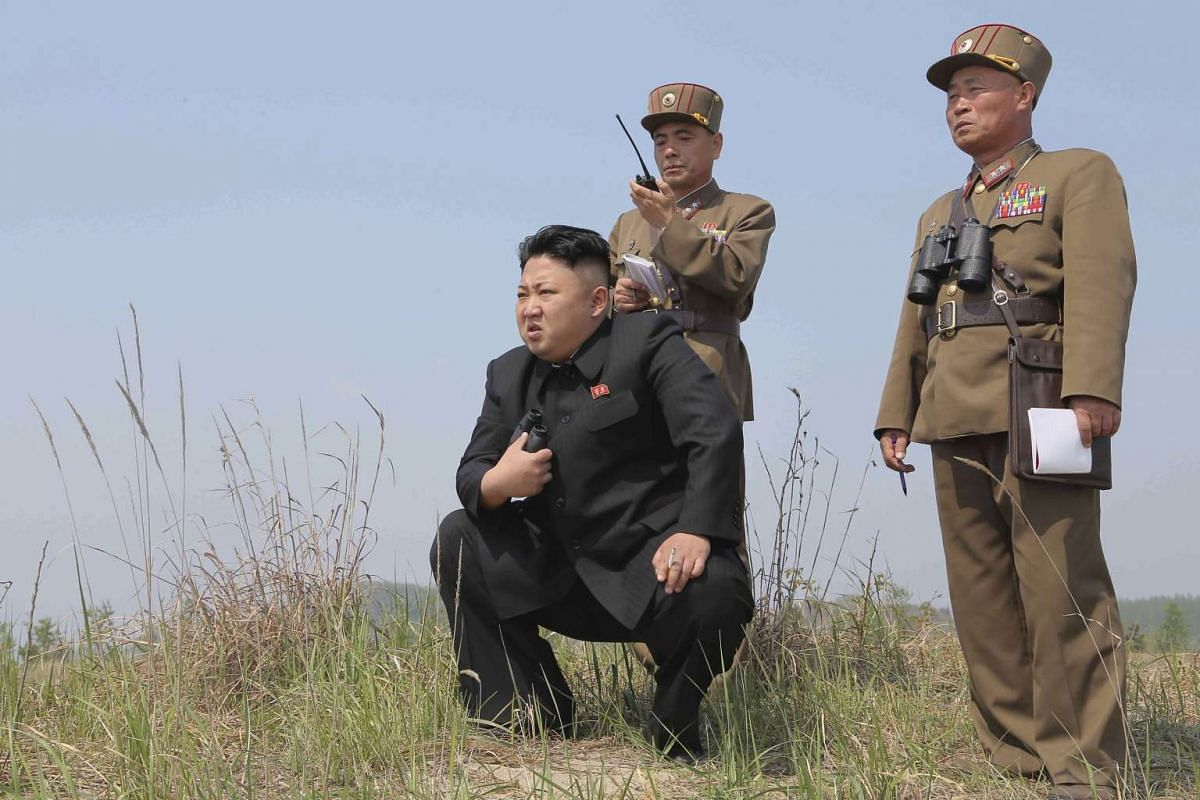 North Korean leader Kim Jong Un (centre) guiding a multiple-rocket launching drill in an undated photo released by the Korean Central News Agency on April 24, 2014.
