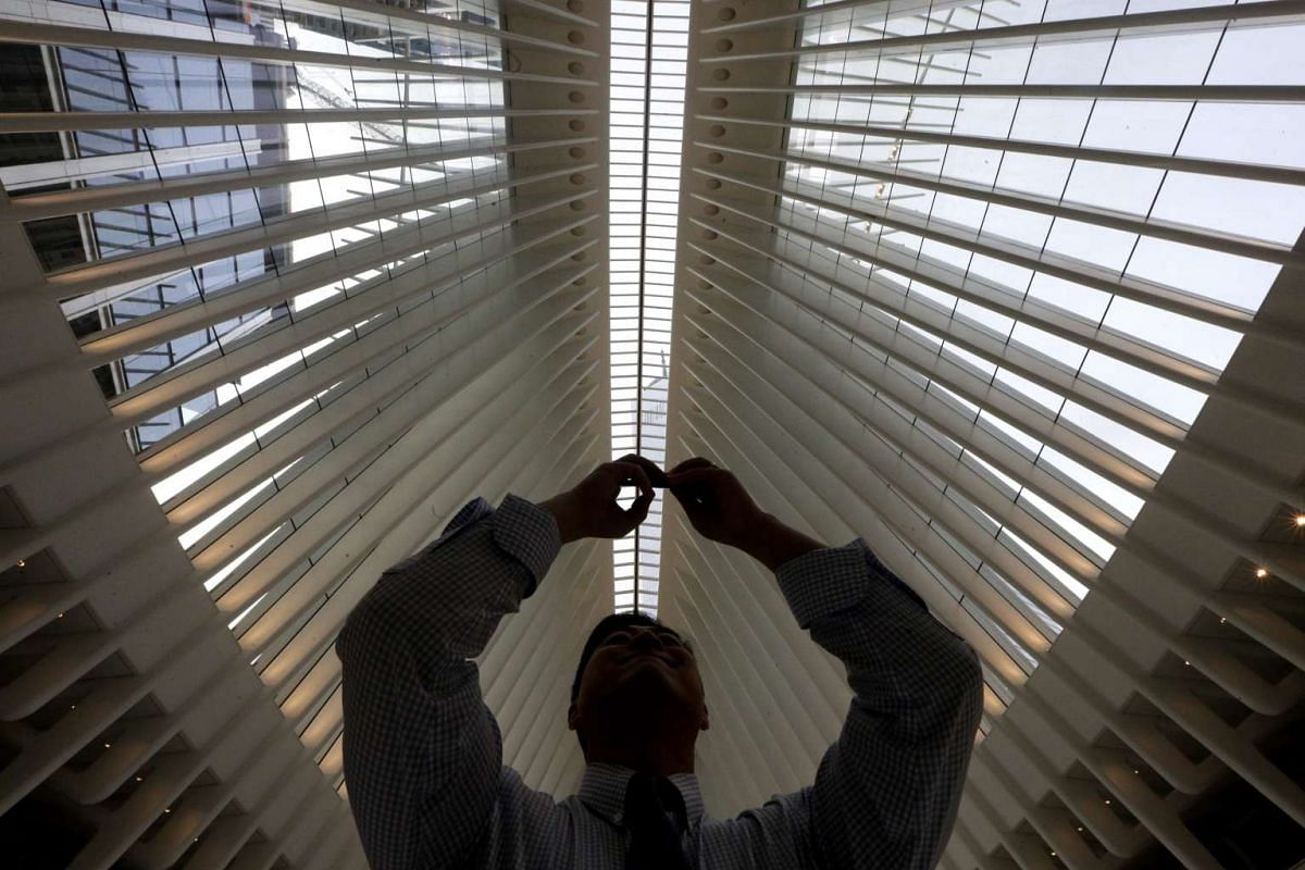A man taking a photo of One World Trade through the roof of the new World Trade Centre transport hub in New York on March 3, 2016.